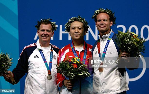 Michael Anti of United States Zhanbo Jia of China and Christian Planer of Austria receive their medals for the men's 50 metre rifle three position...
