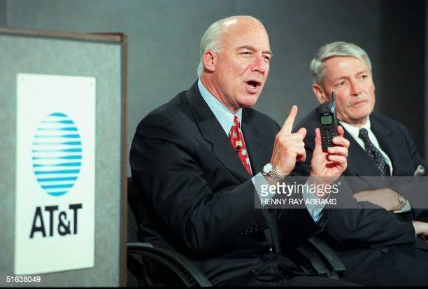 Michael Armstrong Chairman and CEO of ATT holds up a new cellular telephone while describing a new ATT phone service 24 June at a press conference in...