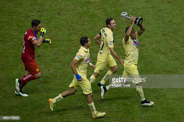 Michael Arroyo lifts the trophy as he celebrates with teammates after winning the final second leg match between America and Tigres UANL as part of...