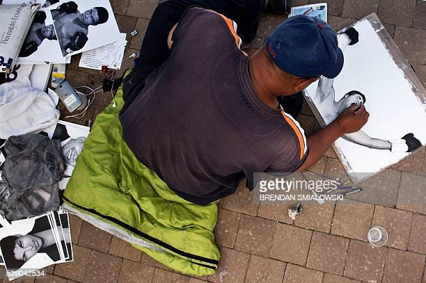 Michael Bailey works on a drawing of boxing legend Muhammad Ali outside the Muhammad Ali Center June 9 2016 in Louisville Kentucky Two days of...