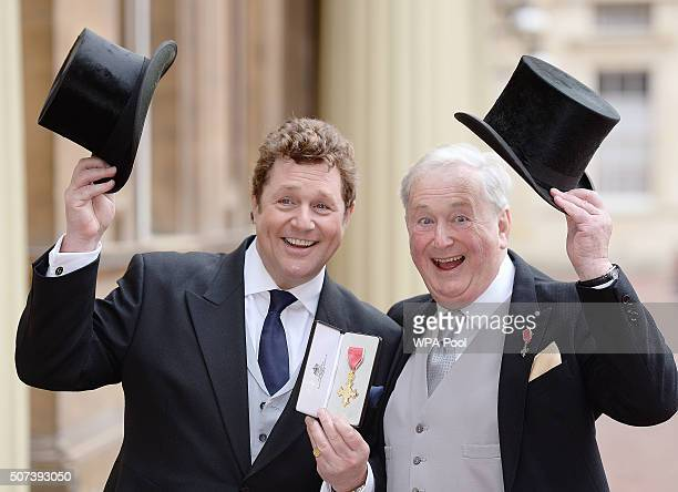 Michael Ball poses with his Officer of the Order of the British Empire medal with his father Tony which was presented to him by the Prince Charles...