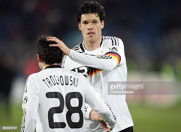Michael Ballack of Germany claps Piotr Trochwoski after the international friendly match between Switzerland and Germany at the St JakobPark on March...