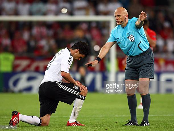 Michael Ballack of Germany gets to his feet as referee Tom Henning Ovrebo awards a free kick during the UEFA EURO 2008 Group B match between Germany...