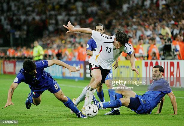 Michael Ballack of Germany is challenged by Gennaro Gattuso and Gianluca Zambrotta of Italy during the FIFA World Cup Germany 2006 Semifinal match...