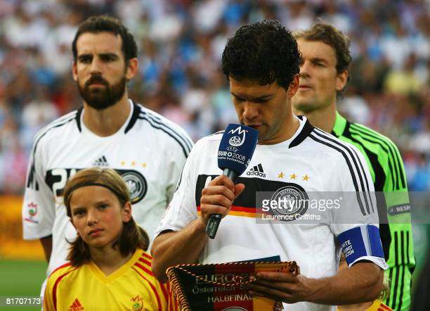 Michael Ballack of Germany reads an antiracism slogan ahead of the UEFA EURO 2008 Semi Final match between Germany and Turkey at St JakobPark on June...