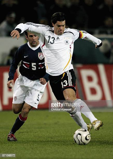 Michael Ballack of Germany runs with the ball and is followed by Kerry Zavagnin of the during the international friendly match between Germany and...
