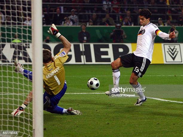 Michael Ballack of Germany scores the second goal against Igor Akinfeev of Russia during the FIFA 2010 World Cup Qualifier match between Germany and...
