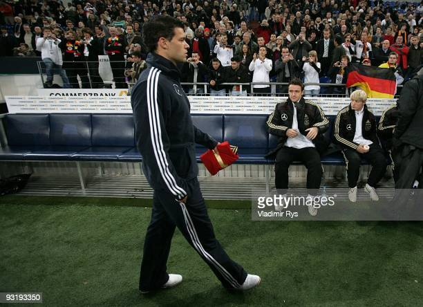 Michael Ballack of Germany walks out with the shirt of German national goalkeeper Robert Enke ahead of the international friendly match between...