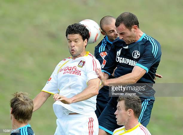 Michael Ballack of Leverkusen battles for the ball with Christoph Metzelder and Nicolas Plestan of Schalke during the friendly match between FC...