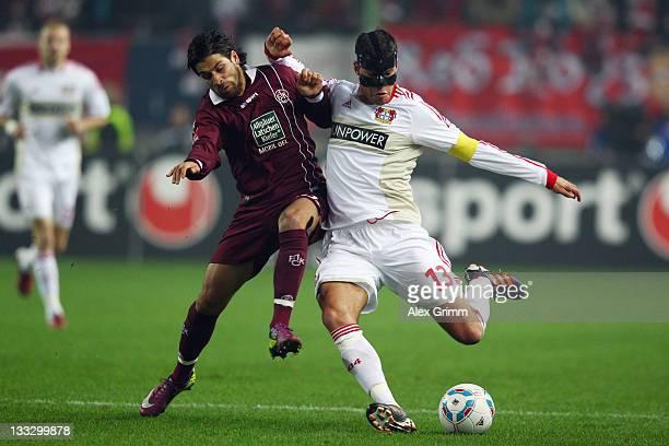 Michael Ballack of Leverkusen is challenged by Olcay Sahan of Kaiserslautern during the Bundesliga match between 1. FC Kaiserslautern and Bayer 04...