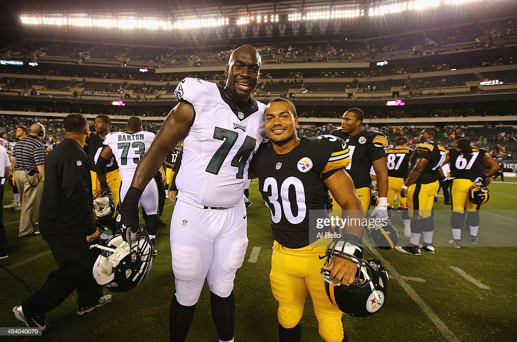 Michael Bamiro #74 of the Philadelphia Eagles and Miguel Maysonet #30 of the Pittsburgh Steelers pose after their Pre Season game at Lincoln Financial Field on August 21, 2014 in Philadelphia, Pennsylvania. They were former roomatesa t Stony Brook University