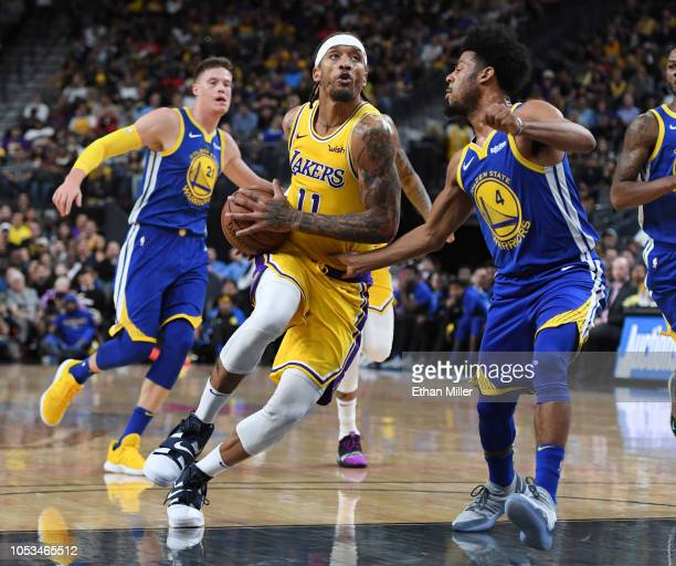 Michael Beasley of the Los Angeles Lakers drives to the basket against Quinn Cook of the Golden State Warriors during their preseason game at TMobile...