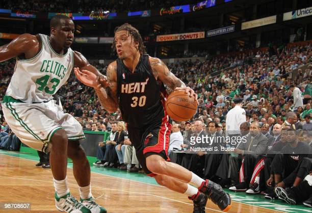 Michael Beasley of the Miami Heat drives against Kendrick Perkins of the Boston Celtics in Game Five of the Eastern Conference Quarterfinals during...