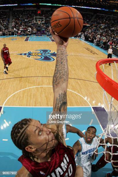 Michael Beasley of the Miami Heat grabs a rebound over Marcus Thornton of the New Orleans Hornets at New Orleans Arena on December 30 2009 in New...