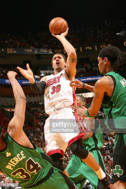 Michael Beasley of the Miami Heat shoots against Paul Pierce of the Boston Celtics on March 11 2009 at the American Airlines Arena in Miami Florida...