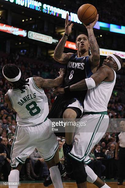 Michael Beasley of the Minnesota Timberwolves is called for an offensive foul as he drives to the net and knocks into Marquis Daniels and Jermaine...