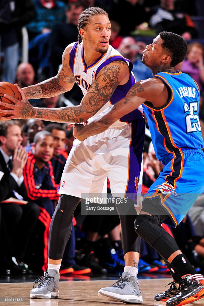 Michael Beasley #0 of the Phoenix Suns controls the ball against DeAndre Liggins #25 of the Oklahoma City Thunder on January 14, 2013 at U.S. Airways Center in Phoenix, Arizona.