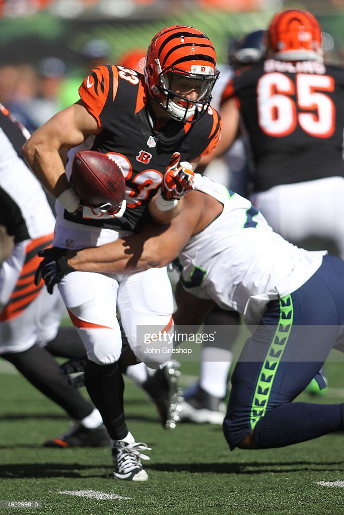 Michael Bennett #72 of the Seattle Seahawks hits Rex Burkhead #33 of the Cincinnati Bengals, forcing a fumble during the third quarter at Paul Brown Stadium on October 11, 2015 in Cincinnati, Ohio.