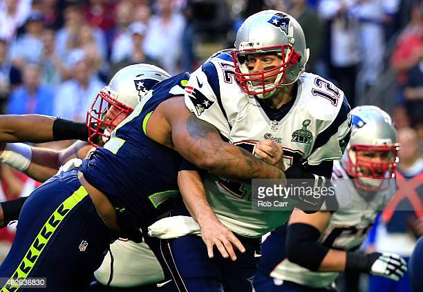 Michael Bennett of the Seattle Seahawks hits Tom Brady of the New England Patriots in the first quarter during Super Bowl XLIX at University of...