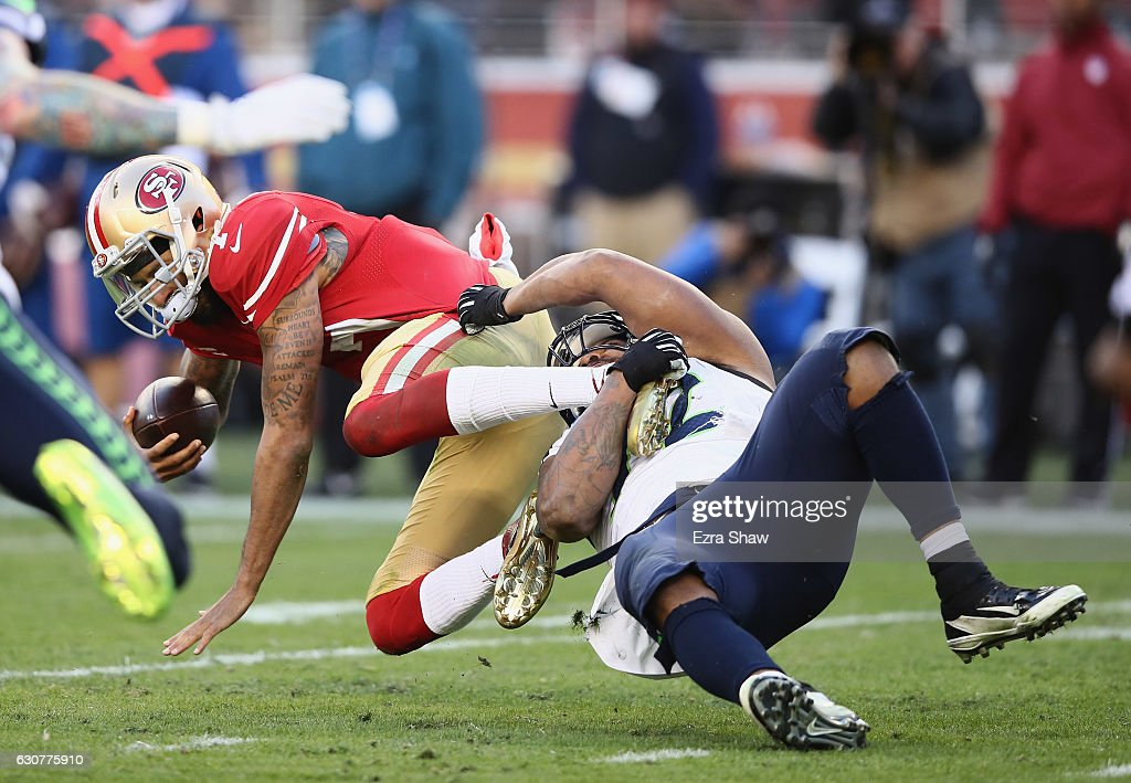 Michael Bennett #72 of the Seattle Seahawks tackles Colin Kaepernick #7 of the San Francisco 49ers at Levi's Stadium on January 1, 2017 in Santa Clara, California.