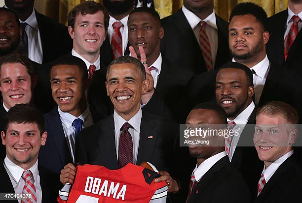 Michael Bennett upper left of the Ohio State University Buckyes football team holds up fingers behind the head of US President Barack Obama during an...
