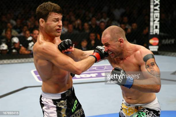 Michael Bisping of England exchanges punches with Alan Belcher in their middleweight bout during the UFC 159 event at the Prudential Center on April...
