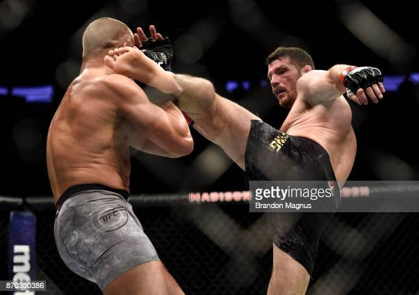 Michael Bisping of England kicks Georges StPierre of Canada in their UFC middleweight championship bout during the UFC 217 event inside Madison...