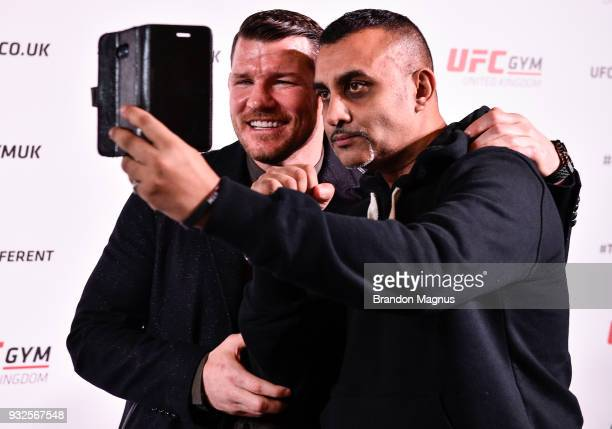 Michael Bisping of England takes a picture with a fan during the UFC Gym Press Conference in Glaziers Hall on March 15 2018 in London England