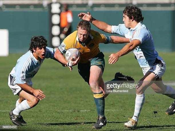 Michael Black of Australia carries the ball under pressure from Nicolas Bruzzone and Horacio Aguila of Argentina during a semifinals match of IRB...