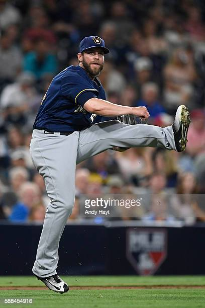 Michael Blazek of the Milwaukee Brewers fields a bunt and throws to first base during the first inning of a baseball game against the San Diego...