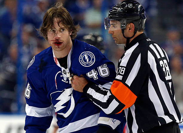 Michael Blunden of the Tampa Bay Lightning is escorted off the ice by referee...