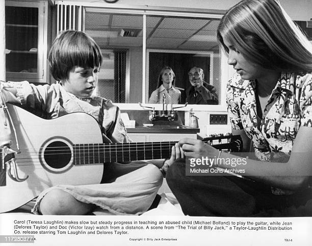 Michael Bolland plays guitar with the help of Teresa Laughlin in a scene from the film 'The Trial of Billy Jack' 1974