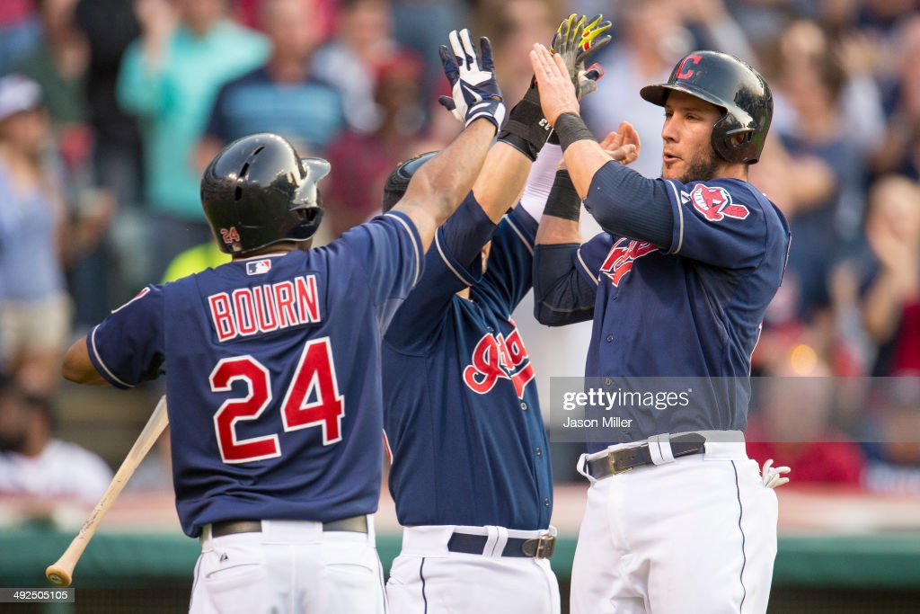 Michael Bourn #24 and Nick Swisher #33 of the Cleveland Indians celebrate with Yan Gomes #10 after Gomes scored during the second inning against the Detroit Tigers at Progressive Field on May 20, 2014 in Cleveland, Ohio.