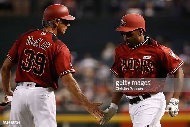 Michael Bourn of the Arizona Diamondbacks highfives first base coach Dave McKay after a sacrifice bunt against the San Francisco Giants during the...