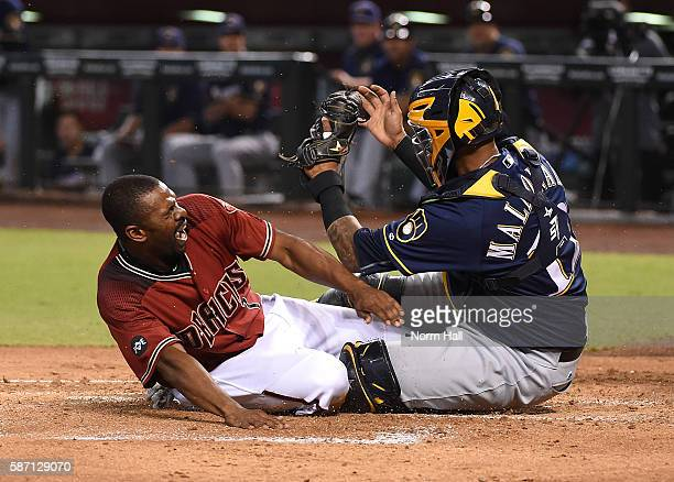 Michael Bourn of the Arizona Diamondbacks is tagged out at home plate by Martin Maldonado of the Milwaukee Brewers during the first inning at Chase...