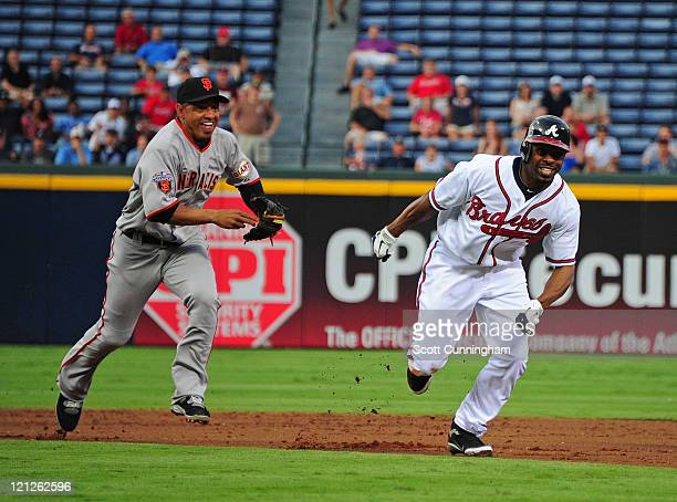 Michael Bourn of the Atlanta Braves gets caught in a rundown with Orlando Cabrera of the San Francisco Giants at Turner Field on August 16 2011 in...