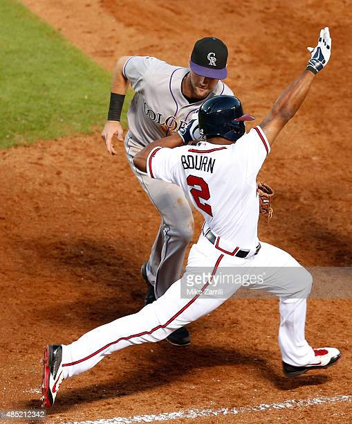 Michael Bourn of the Atlanta Braves is tagged out by first baseman Ben Paulsen of the Colorado Rockies in the third inning during the game at Turner...