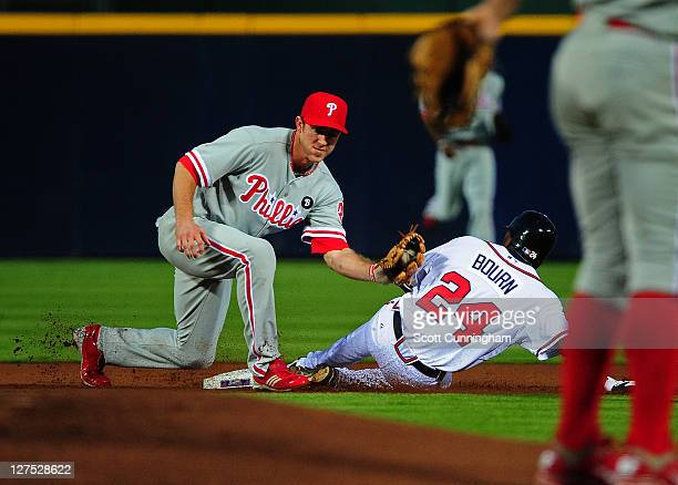 Michael Bourn of the Atlanta Braves steals second base against Chase Utley of the Philadelphia Phillies at Turner Field on September 28 2011 in...