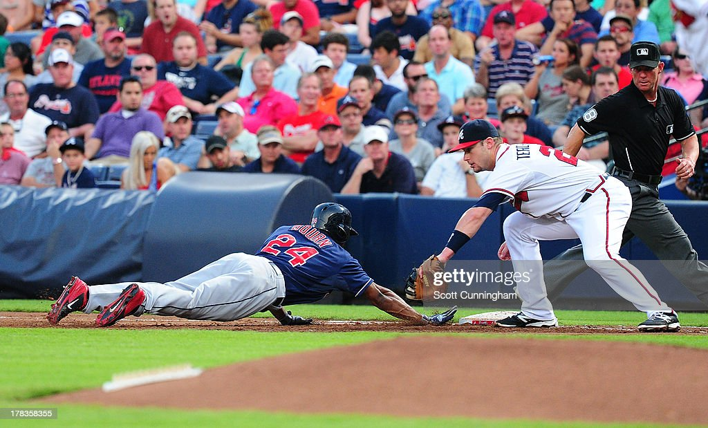 Michael Bourn #24 of the Cleveland Indians dives back safely to first base against Joey Terdoslavich #25 of the Atlanta Braves at Turner Field on August 29, 2013 in Atlanta, Georgia.