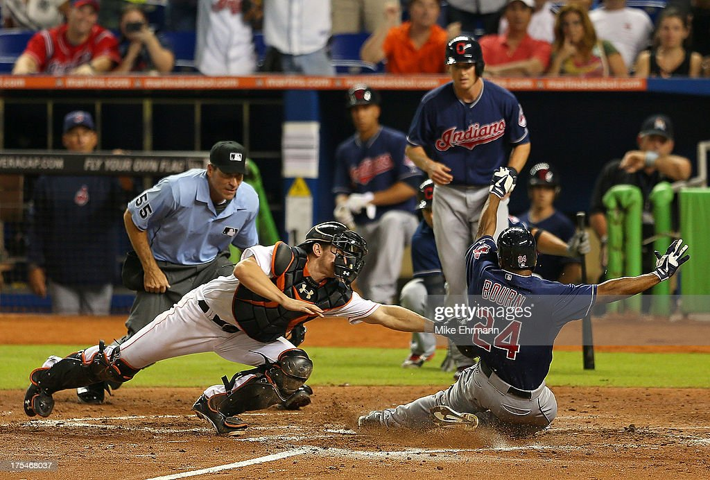 Michael Bourn #24 of the Cleveland Indians slides past the tag from Rob Brantly #19 of the Miami Marlins during a game at Marlins Park on August 3, 2013 in Miami, Florida.