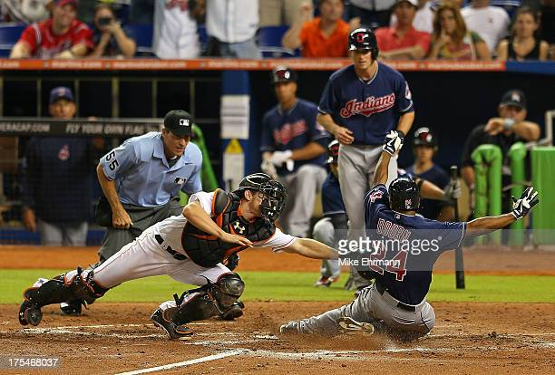 Michael Bourn of the Cleveland Indians slides past the tag from Rob Brantly of the Miami Marlins during a game at Marlins Park on August 3 2013 in...