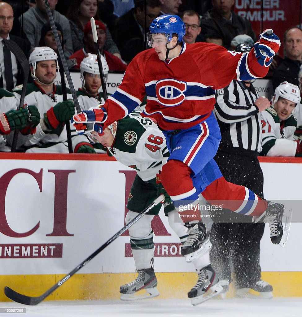 Michael Bournival #49 of the Montreal Canadiens jumps while racing against Jared Spurgeon #46 of the Minnesota Wild during the NHL game on November 19, 2013 at the Bell Centre in Montreal, Quebec, Canada.