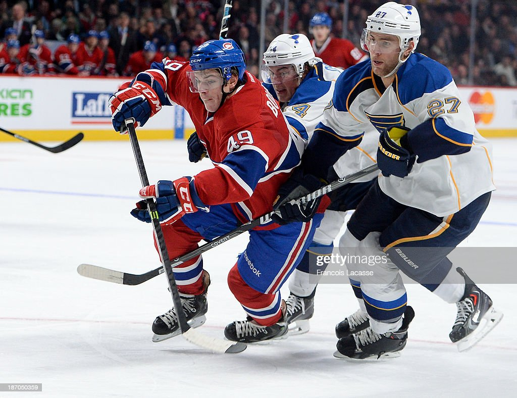 Michael Bournival #49 of the Montreal Canadiens skates for the puck, while being challenged by Alex Pietrangelo #27 and T.J. Oshie #74 of the St. Louis Blues during the NHL game on November 5, 2013 at the Bell Centre in Montreal, Quebec, Canada.