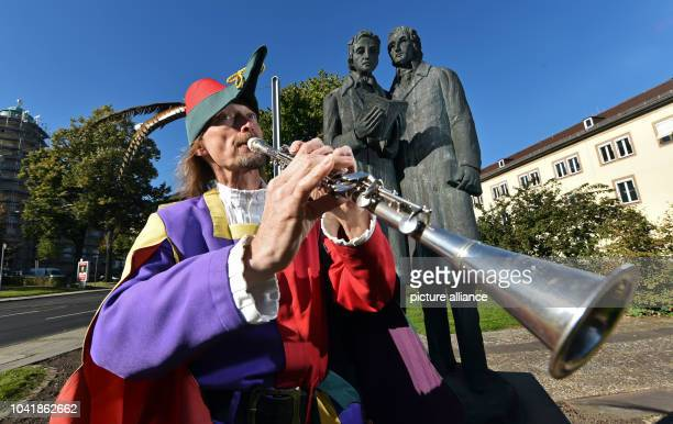 Michael Boyer dressed up as the Pied Piper of Hamelin plays his magic pipe in front of the memorial for the brothers Wilhelm and Jacob Grimm in...