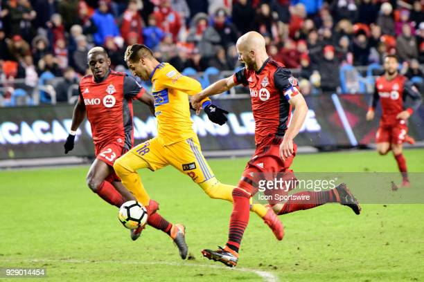 Michael Bradley and Chris Mavinga of Toronto FC attempt to stop Ismael Sosa of Tigres UANL during extra time of the second half of the CONCACAF...