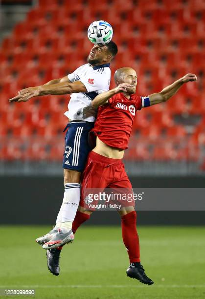 Michael Bradley of Toronto FC battles for a header with Lucas Cavallini of Vancouver Whitecaps FC during the second half of an MLS game at BMO Field...