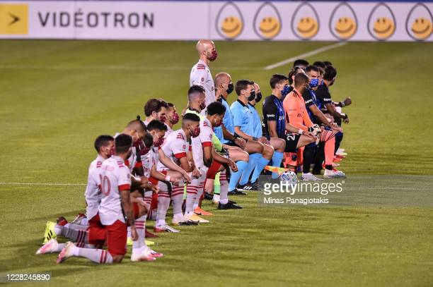 Michael Bradley of Toronto FC stands while his teammates and members of the Montreal Impact kneel during the pregame ceremony of the MLS game at...