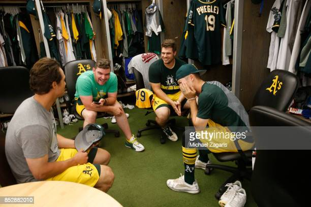Michael Brady Liam Hendriks Josh Phegley and Daniel Gossett of the Oakland Athletics talk in the clubhouse prior to the game against the Los Angeles...