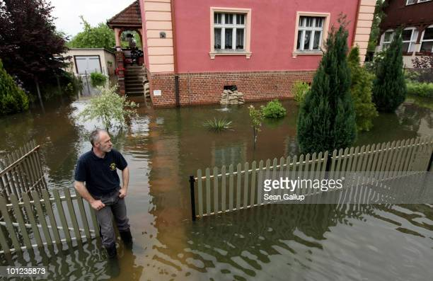 Michael Brandenburg stands outside his sandbagged home as a pump shoots out floodwater from his basement on May 28 2010 in Frankfurt Germany The Oder...