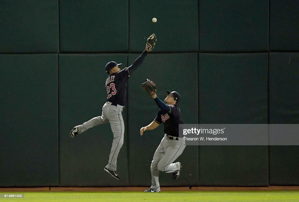 Michael Brantley #23 and Bradley Zimmer #4 of the Cleveland Indians avoid colliding with each other going after a ball that bounces off the wall for a triple off the bat of Matt Chapman #26 of the Oakland Athletics in the bottom of the seventh inning at Oakland Alameda Coliseum on July 14, 2017 in Oakland, California.